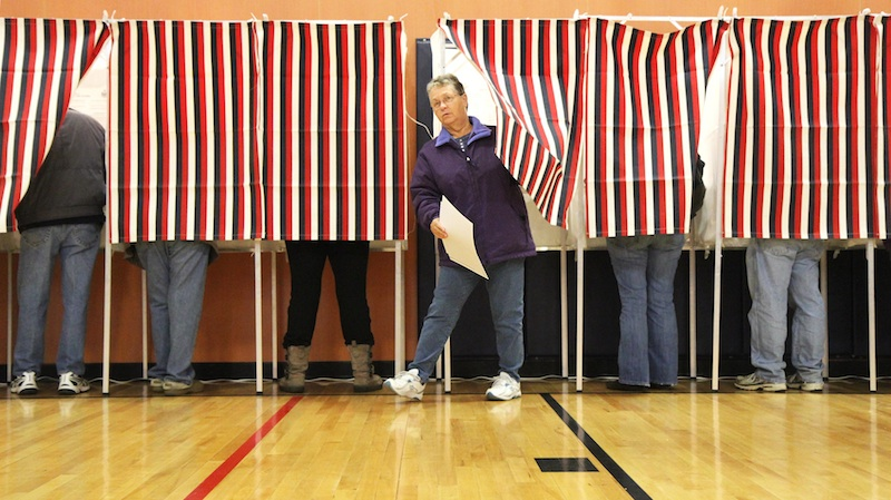 Jeannette Garland leaves a voting booth before casting her ballot at Mill Stream Elementary School in Norridgewock on Tuesday.