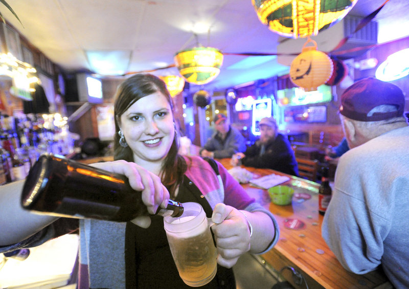 Bartender Clare Finin pours a beer into a frosty mug at Sangillo's Tavern, a small, friendly bar with affordable prices in the India Street neighborhood of Portland.