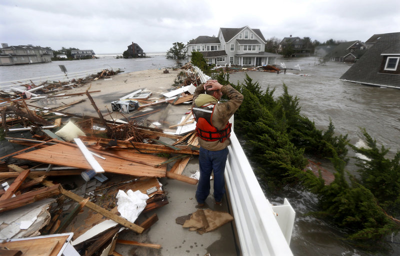 Brian Hajeski, 41, of Brick, New Jersey, reacts as he looks at debris of a home that washed up on to the Mantoloking Bridge after Hurricane Sandy rolled through.