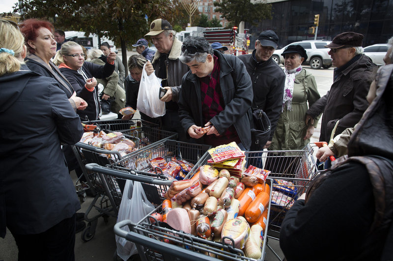 People shop for food piled into shopping carts in Brooklyn, N.Y., after Hurricane Sandy closed stores.