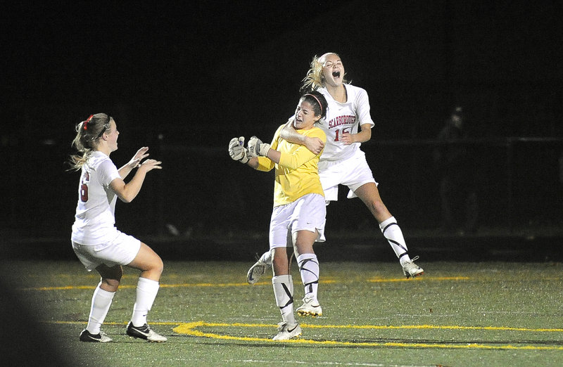 It's time to celebrate for the Scarborough girls' soccer team as Sam Sparda, left, and Ainsley Jamieson, right, mob goalie Sydney Martin after a 1-0 win over Cape Elizabeth Wednesday for the Western Class A girls' championship.