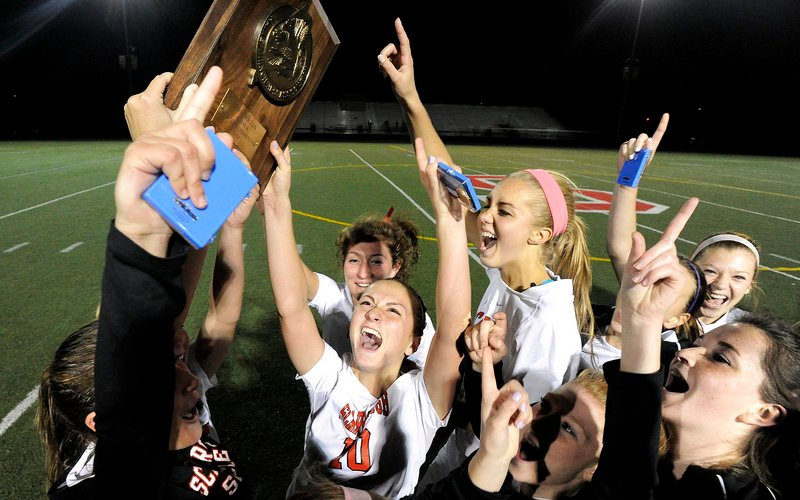 The Scarborough High girls hoist the trophy after beating Cape Elizabeth 1-0 for the Western Class A championship Wednesday.