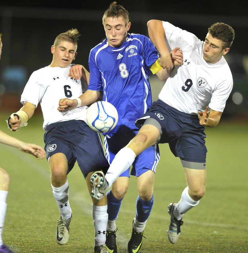 Mike Smith, left, and Max Watson of Yarmouth try to squeeze out Falmouth's Cooper Lycan to gain control of the ball in Wednesday night's Western Class B championship match. Falmouth produced a 2-0 win.