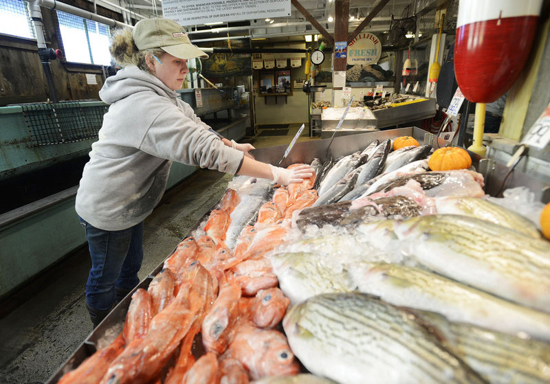 Lauren MacVane stocks the display case at Harbor Fish Market in Portland Thursday. Fish and lobster prices are down due to the lack of demand from buyers in the areas where Sandy knocked out power and did major damage.