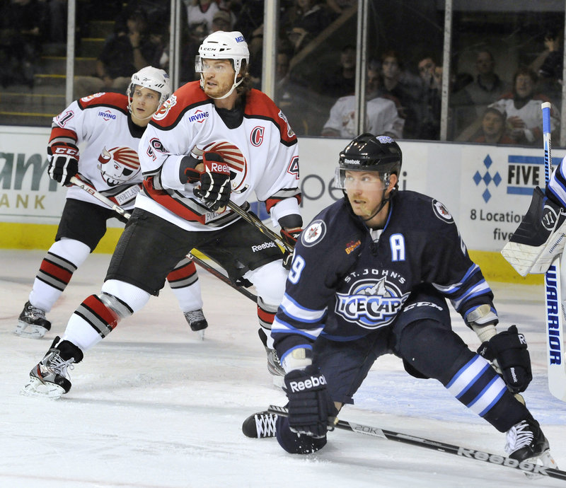 Pirates forward Alexandre Bolduc, center, and IceCaps defenseman Dean Arsene anticipate a shot on goal.