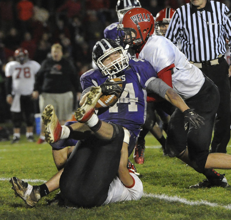 Brett Gerry is brought down – but not for long – by Wells' Ryan Marsh (17) and Dylan Stevens (12) in Friday's Western Class B football semifinal, won by Marshwood.