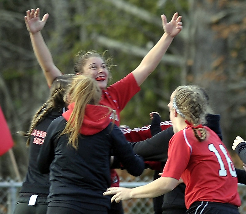 Sarah Martens, rear, is swarmed by her teammates after her overtime goal Saturday gave Scarborough a 2-1 win over Bangor in the C lass A girls' soccer final.