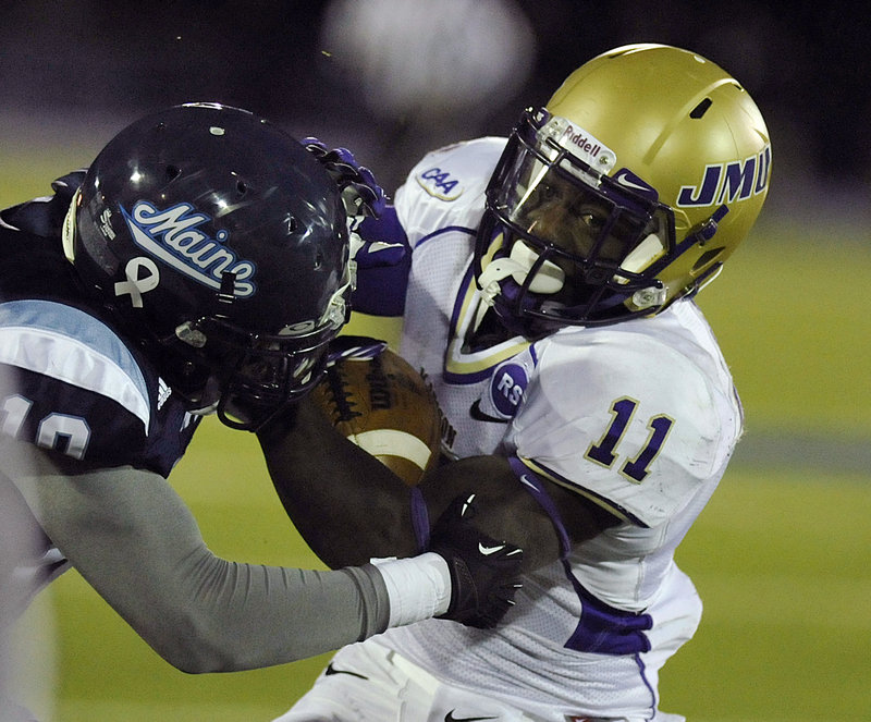 James Madison tailback Dae'Quan Scott tries to eacape the grasp of Maine defender Axel Ofori during Saturday's game in Orono.