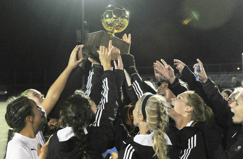 Falmouth players hold the Gold Ball aloft, again, after capturing their third straight Class B girls' soccer state championship Saturday with a 2-1 victory over Hermon.