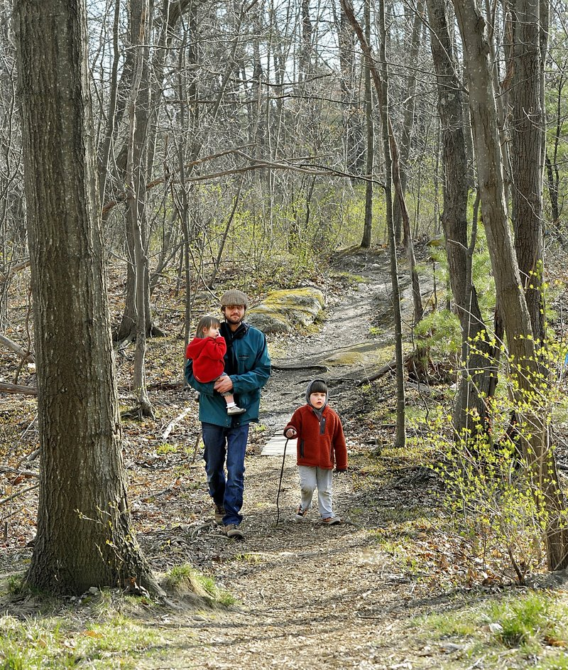 Tim Willoughby, carries his daughter Maeve, 2, and walks with his son Thomas, 4, on a path in the Canco Woods parcel in April. The family lives in Portland's Back Cove area.