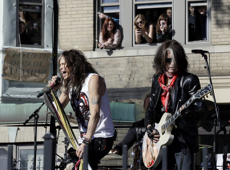 Aerosmith members Steven Tyler, left, and Joe Perry perform Monday, Nov. 5, 2012 in Boston's Allston neighborhood at a free concert by Aerosmith whose band members lived there in the early 1970's. (AP Photo/Elise Amendola)