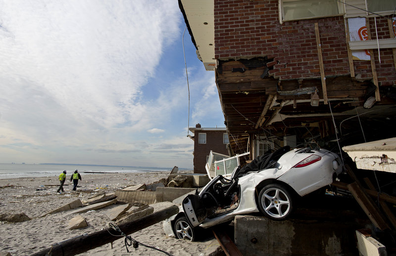 A badly damaged home is entangled with a vehicle along the beach in the Belle Harbor section of the borough of Queens, New York, Monday, Nov. 5, 2012, in the wake of Superstorm Sandy. Temperatures dipped toward freezing early Monday, and tens of thousands of people without power along the ravaged Atlantic coastline faced the prospect of finding somewhere else to stay. (AP Photo/Craig Ruttle)