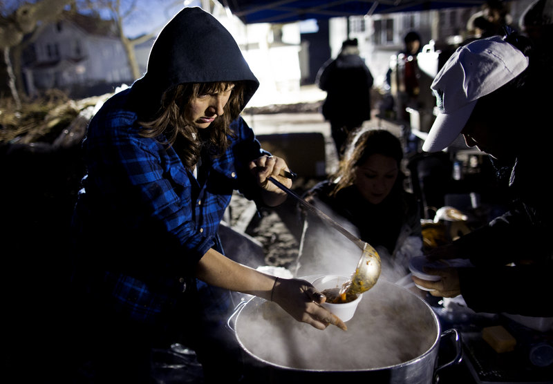 Ariel Nadelberg of Brooklyn pours hot soup in a cup at a parking lot that has become makeshift place for residents to get food and clothing in a Rockaway neighborhood of Queens, N.Y., on Monday. Many volunteers have shown up on their own to try to lend a hand any way they can.
