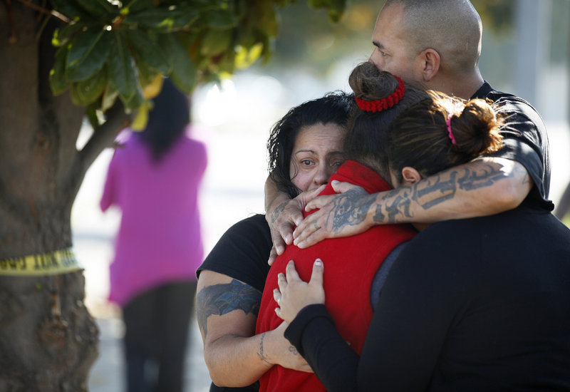Three women and a man hug outside the police perimeter in central Fresno where a shooting occurred at a workplace Tuesday. A parolee who worked at a California chicken processing plant opened fire at the business, killing two people and wounding three others.