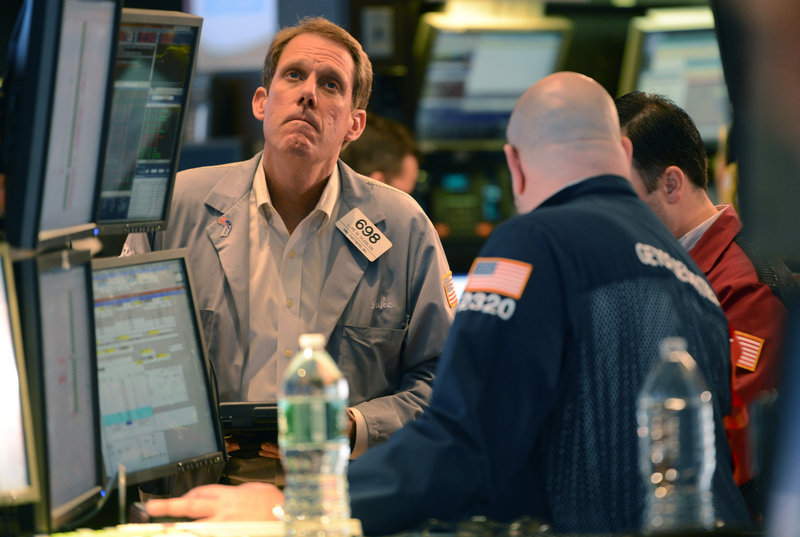 Luke Scanlon of MND Partners Inc. watches stock prices during a volatile day on the floor of the New York Stock Exchange on Wednesday, the day after President Obama was re-elected.