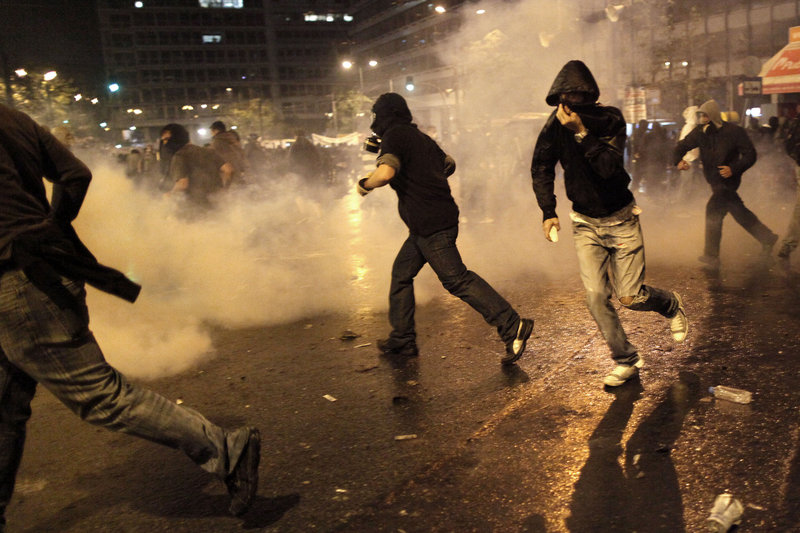 Rioting youths clash with police dispensing tear gas near the Greek parliament Wednesday when the nation's fragile coalition government approved of budget cuts that, among other things, will lead to tax increases as well as further reductions in pensions and salaries.