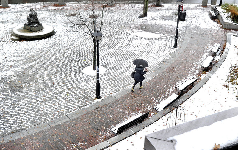 As the first snowfall of the season turns to rain, a pedestrian on Temple Street in Portland uses an umbrella. Most places saw just a few inches of snow before the rains came.