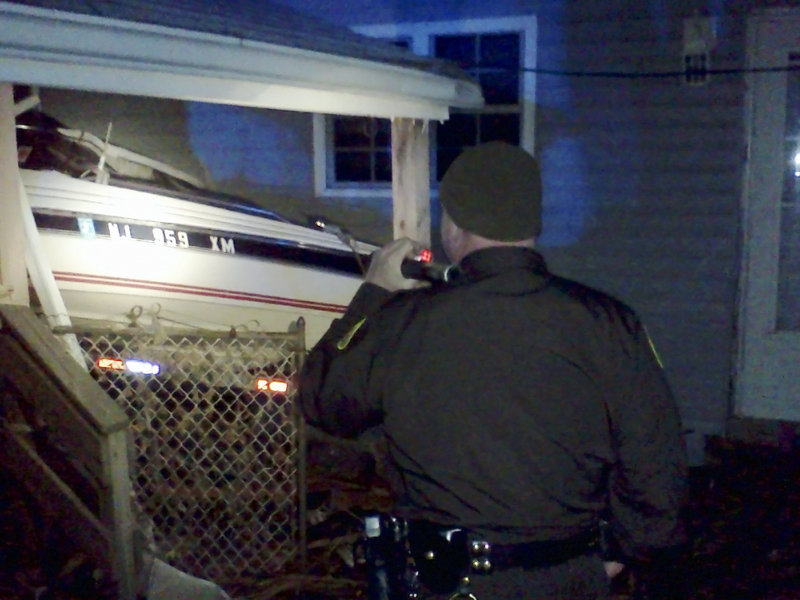 Cumberland County Sheriff's Sgt. James Ambrose inspects a boat in Monmouth County that was washed onto a house porch by Superstorm Sandy. Ambrose and a contingent of Maine officers are helping police patrol the streets and enforce a 6 p.m.-to-6 a.m. curfew.