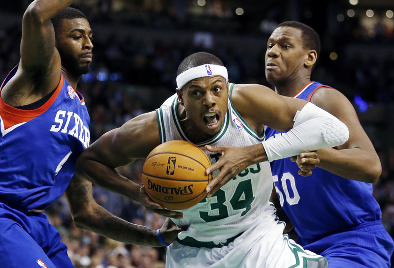 Boston's Paul Pierce makes a determined drive to the basket while guarded by Philadelphia's Dorell Wright, left, and Lavoy Allen during the second quarter of the 76ers' 106-100 win over the Celtics at Boston on Friday night.