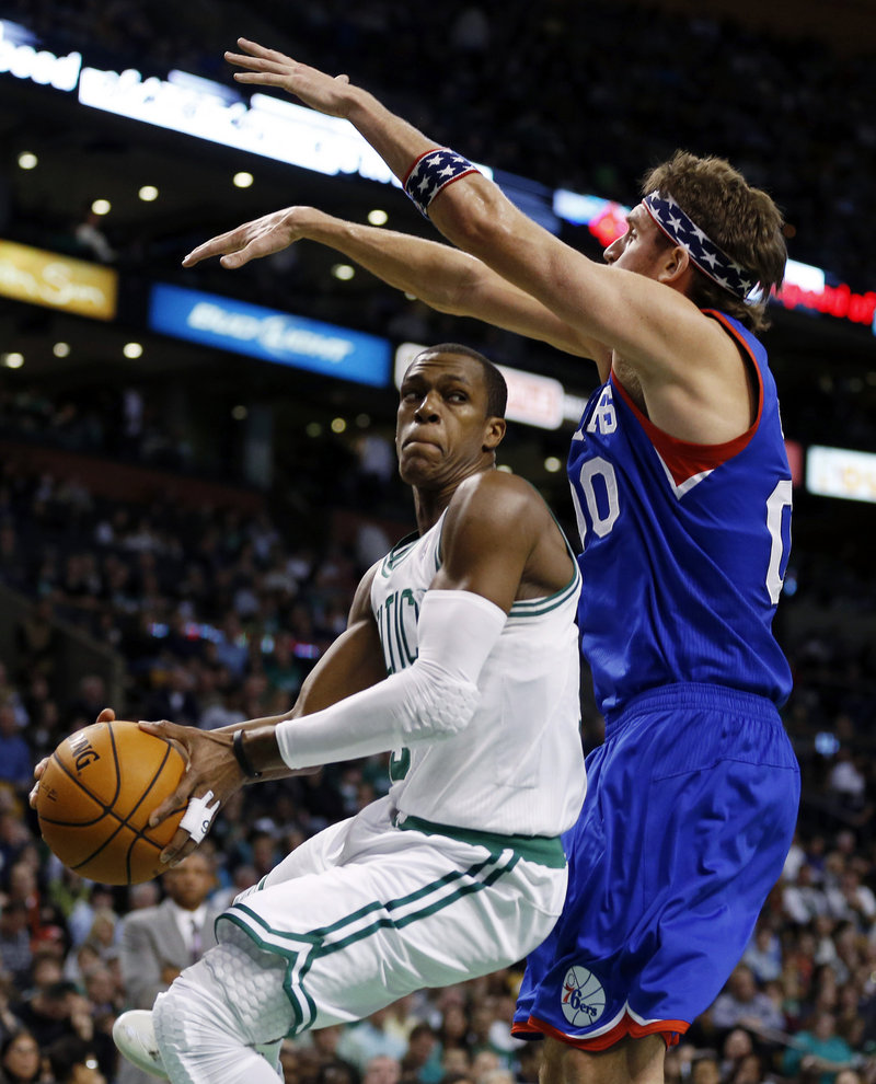Boston's Rajon Rondo, left, makes an inside move against Philadelphia's Spencer Hawes. Rondo finished with 14 points and 20 assists, but the Celtics lost 106-100 and fell to 2-3.