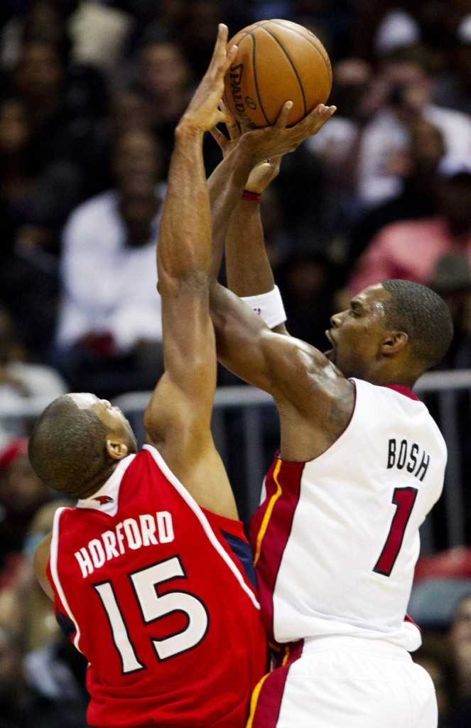 Miami Heat center Chris Bosh, right, has his shot blocked by Atlanta Hawks power forward Al Horford (15) in the first half of a 95-89 win by the Heat at Atlanta.