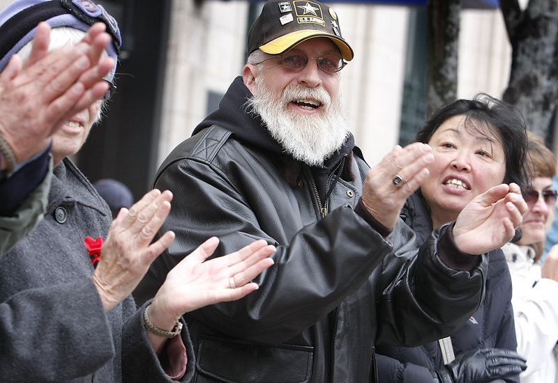Stephen Betters of Portland and his wife, Sun, right, applaud the Portland Veterans Day parade Sunday. Stephen Betters served in the Army from 1973-1993.