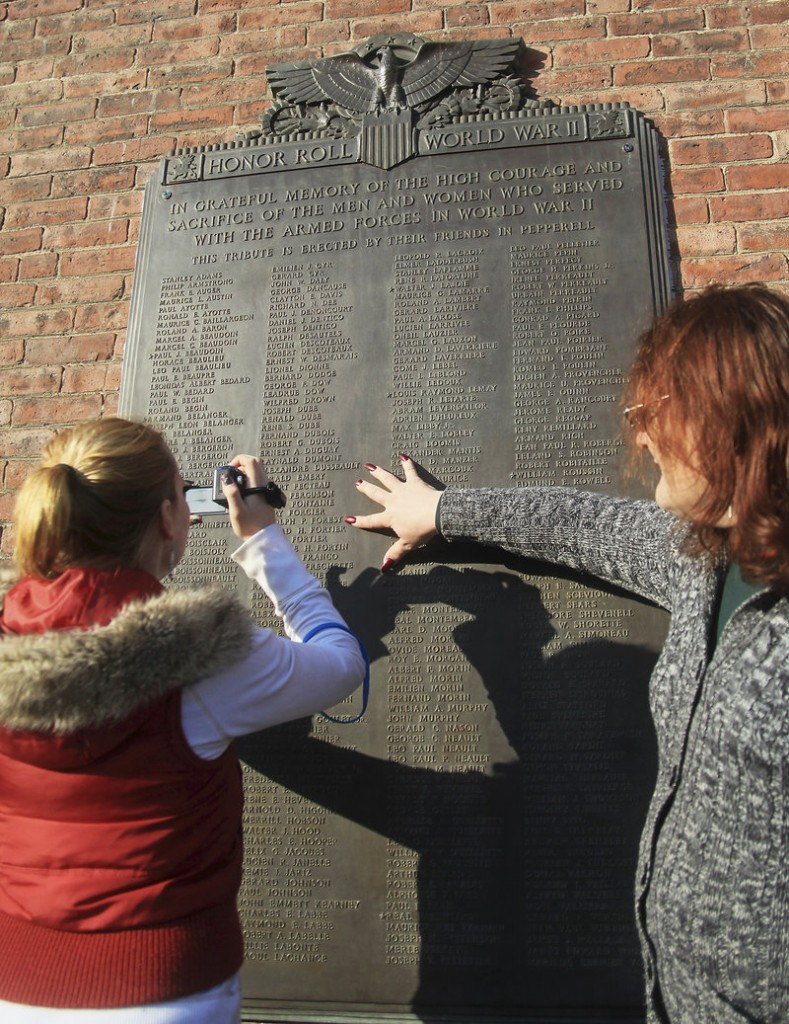 Roger Forest, right, of Old Orchard Beach locates the names of relatives listed on the Pepperell Co.'s World War II plaque as his daughter, Mariah Babine, also of Old Orchard Beach, takes a photograph.