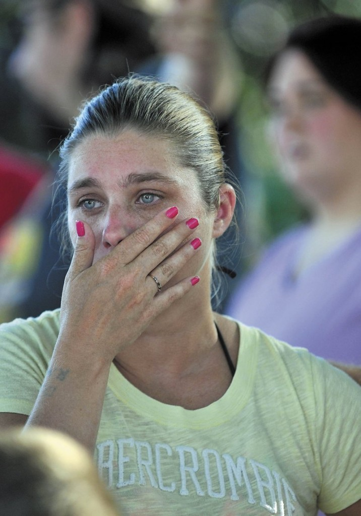 Janet White wipes away tears as she watches her apartment burn in August.