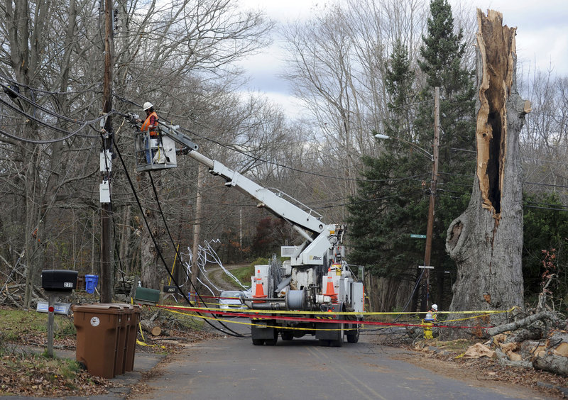 The Associated Press A crew from AT&T repairs lines near the remains of a 400-year-old oak tree in Shelton, Conn., which was toppled by wind gusts during Hurricane Sandy.