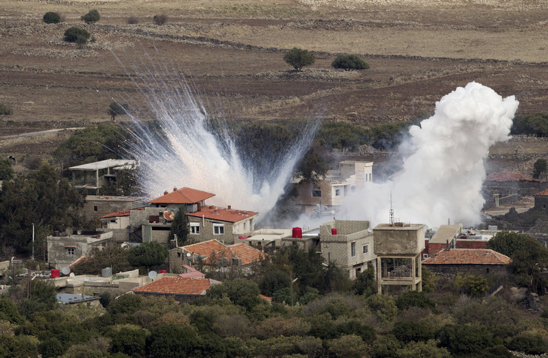 "Smoke rises after shells fired by the Syrian army explode in the Syrian village of Bariqa. Israel said ""Syrian mobile artillery"" was hit after Israel responded to stray mortar fire."