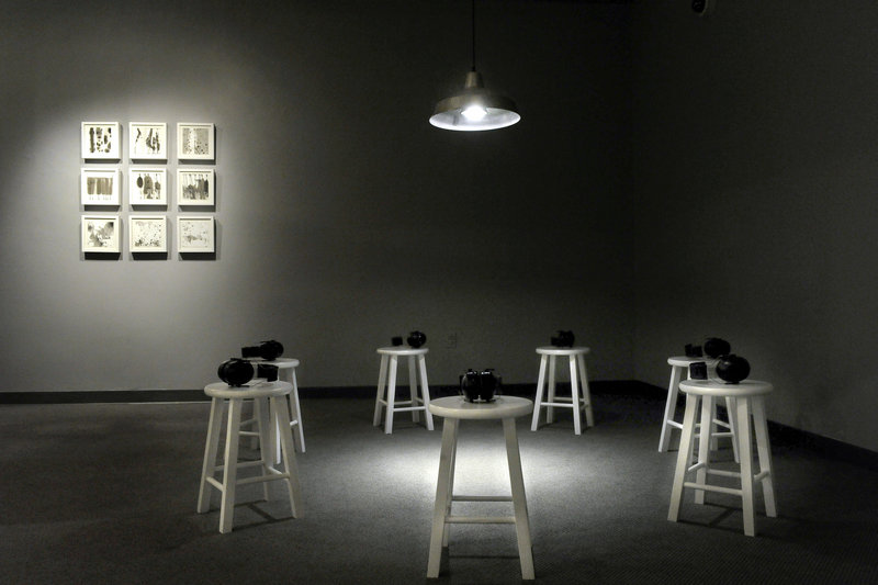 """Two installations by Ling-Wen Tsai, including """"Residual 1-9,"""" sumi ink on paper, on the wall at left."""