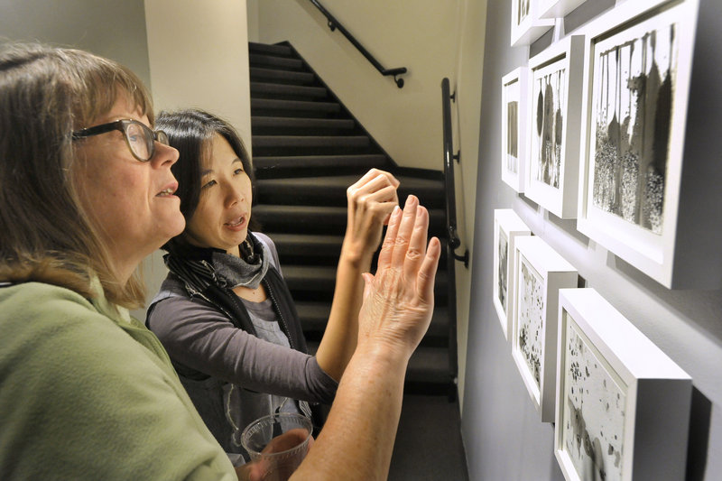 "Ling-Wen Tsai discusses her work ""Residual 1-9"" with art student Diane Morin of Augusta."
