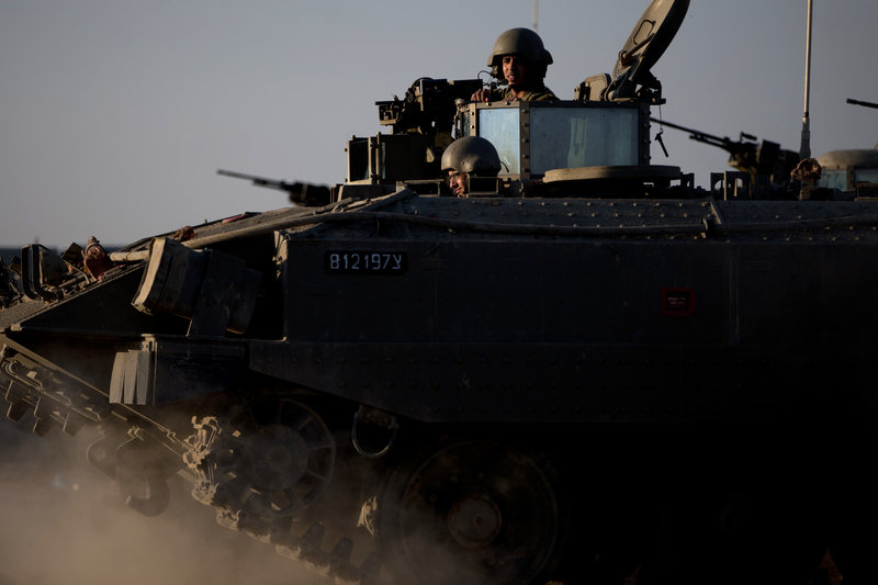 "Israeli soldiers ride on an armored personnel carrier near the Gaza border Thursday. Israel's prime minister says the army is prepared for a ""significant widening"" of its Gaza offensive."