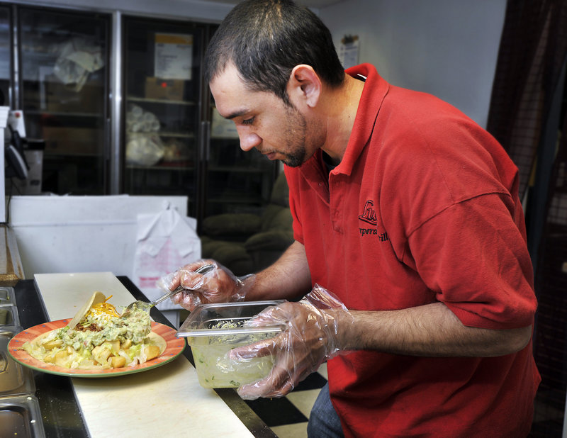 Luis Sanchez composes a plate of chicken arepa and fried yucca.