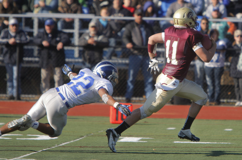 Thornton Academy quarterback Eric Christensen eludes a dive by Xavier Lewis of Lawrence and heads into the end zone to score on a 30-yard run Saturday – part of the spurt that produced a 37-23 victory in the Class A final at Fitzpatrick Stadium.