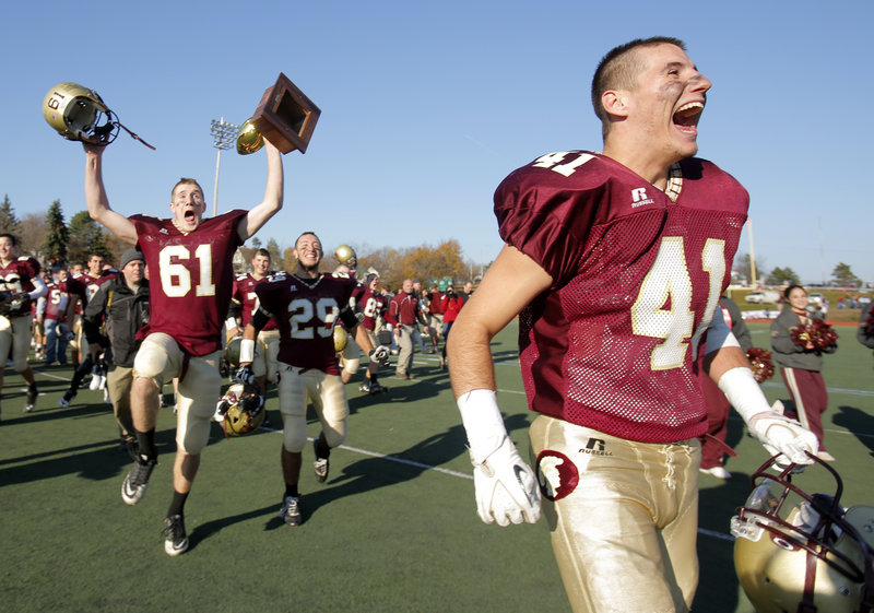 Jordan Matthews, left, can't contain his excitement about getting a chance to hold the Gold Ball as Alex Rizeakos, center, Joshua Cyr, right, and the rest of the Thornton Academy football team celebrate their victory Saturday over Lawrence in the Class A state championship game.
