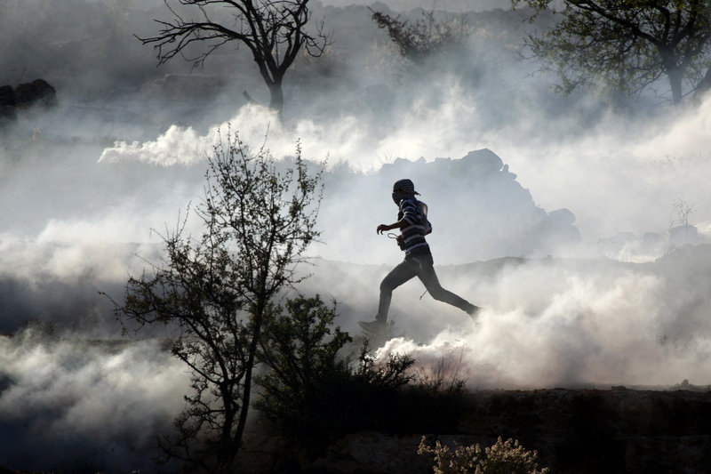 A Palestinian demonstrator runs through tear gas Thursday during clashes against Israel's operations in the Gaza Strip outside Ofer, an Israeli military prison near Ramallah.