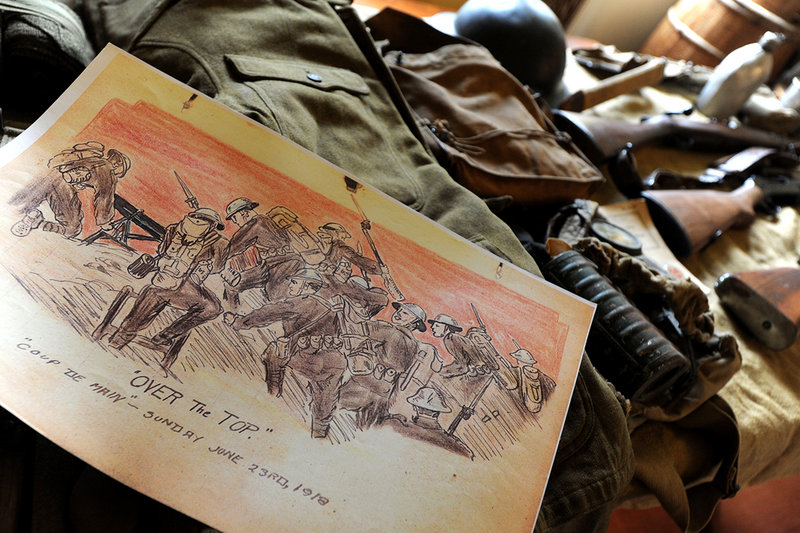 In this Friday, Nov. 2, 2012 photo John Mayo, 76, looks though artwork produced by his father WW I U.S. Army Pfc. Frederick Mayo, at the Lafayette-Durfee House, in Fall River, Mass. Drawings by Mayo, who for 26 months was one of the