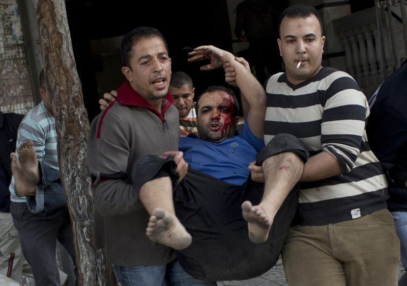Palestinians carry injured people out of a media center in Gaza City that was hit by an Israeli strike for the second time in two days Monday. A senior militant was killed in the strike.