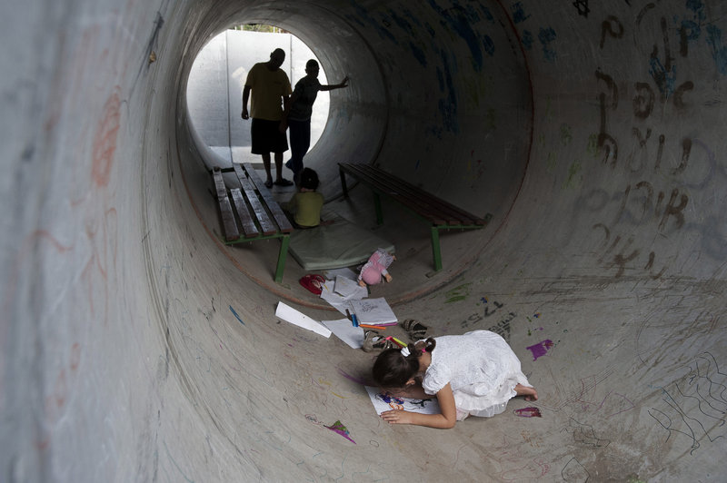 Israelis hide in a concrete tube during a rocket attack from Gaza, in Nitzan, southern Israel, on Monday.