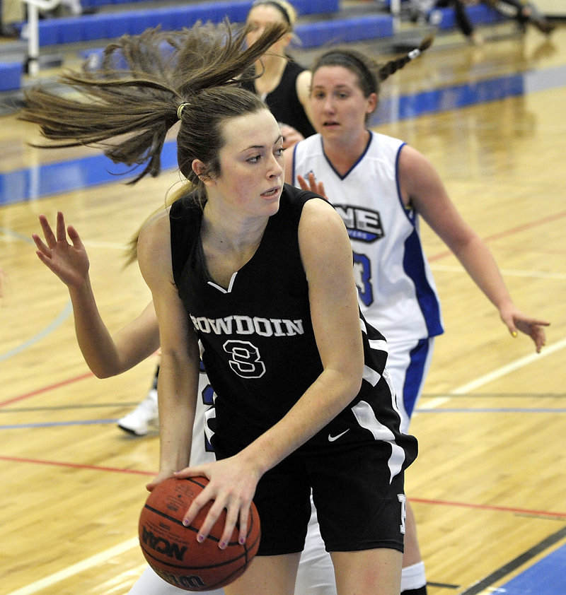 Shannon Brady of Bowdoin looks for a teammate to start the transition game after grabbing a rebound against UNE. Bowdoin dropped to 1-2; UNE is 2-1.