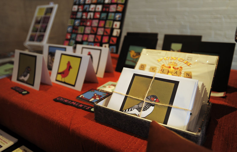 Arts and crafts by Mandy Sabine and other local artisans are displayed on a table at Engine's storefront in downtown Biddeford.