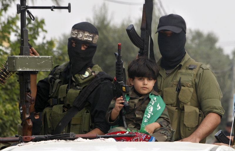 A Palestinian boy and militants of the Izzedine Al-Qassam Brigades attend funerals in central Gaza Strip of five Hamas militants killed in an Israeli airstrike.
