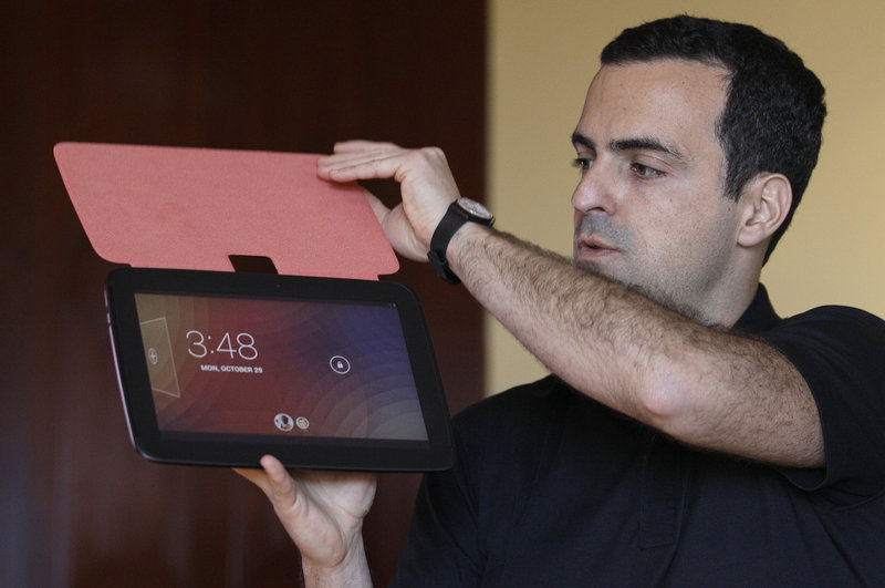 Hugo Barra of Google holds up the new Nexus 10 tablet, which beats the iPad's screen resolution.