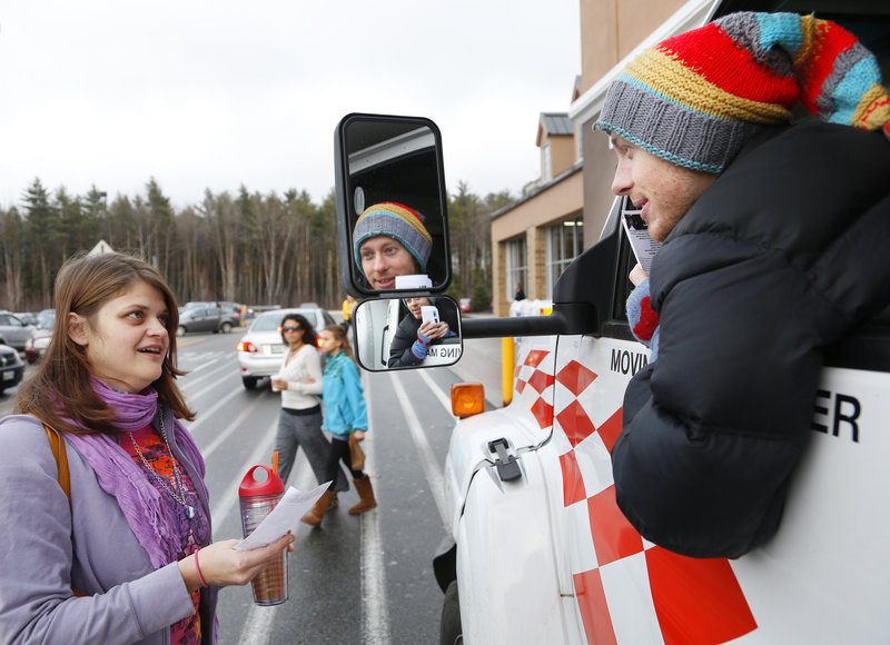 William Hessian of Portland leans out of the moving truck at Walmart in Scarborough to talk to Crystal Golling of Portland about the donations that they are taking to be distributed to victims of Hurricane Sandy in New York City.