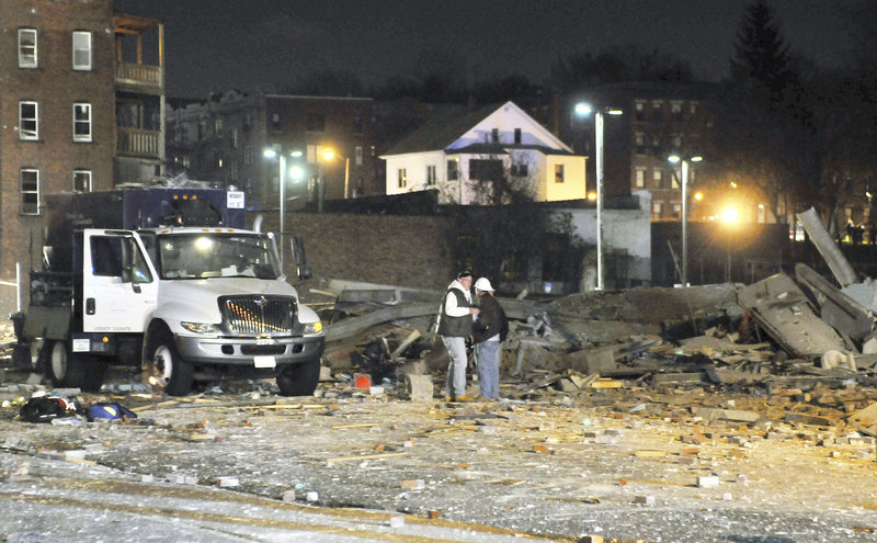 Gas company workers stand where a building once stood, which was leveled by an explosion in downtown Springfield, Mass. on Friday, Nov. 23, 2012. (AP Photo/Springfield Republican, Don Treeger)