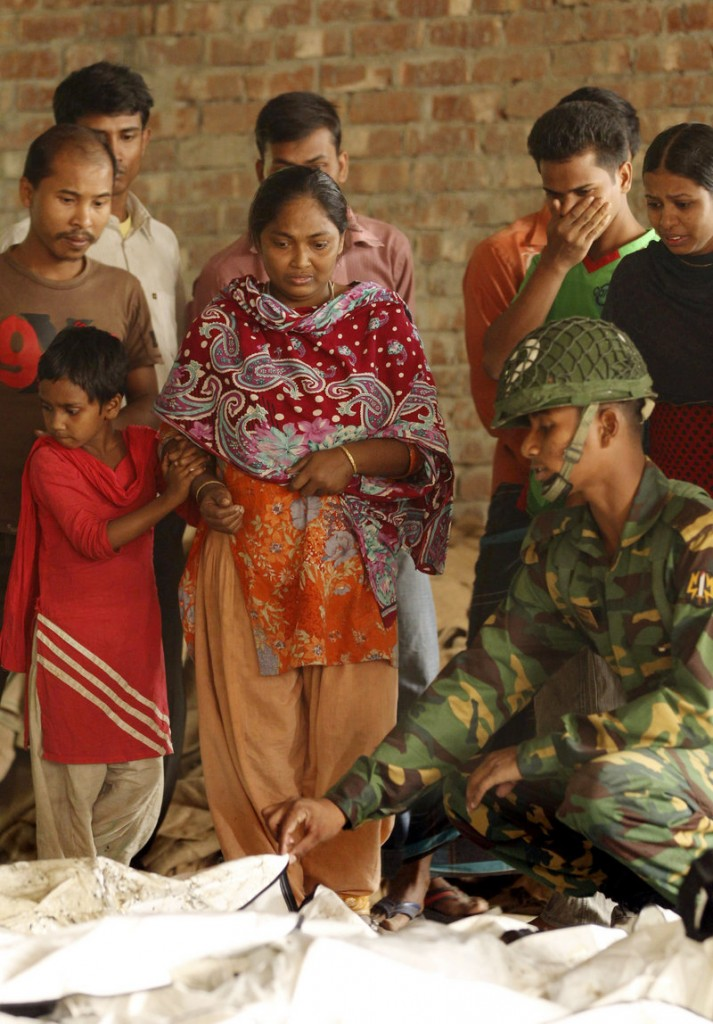 A Bangladeshi army soldier helps people identify the bodies of their relatives killed in a fire at a garment factory outside Dhaka on Sunday.