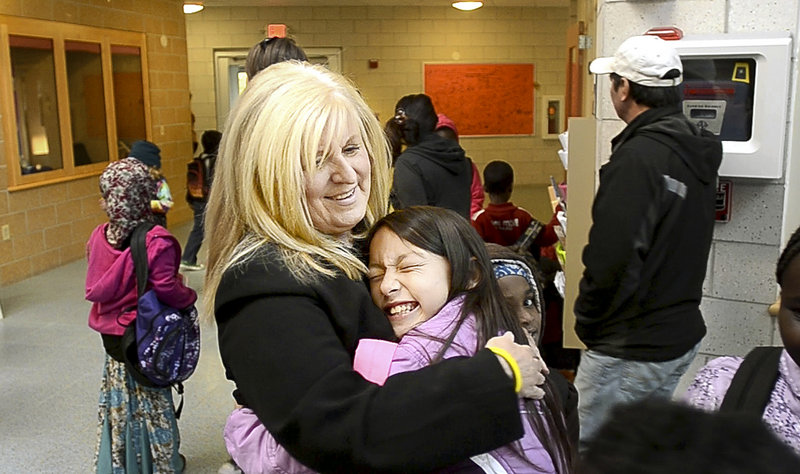 Marcia Gendron, principal of East End Community School in Portland, gets a hug from third-grader Maureen Fitzgerald at the start of a school day. Most of the 410 students come from racially diverse and poor neighborhoods.