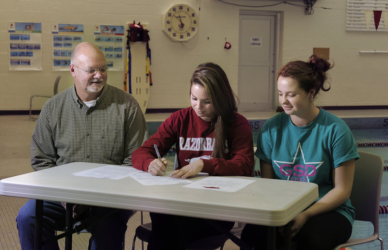 Sarah Easterling, center, singing a letter of intent to attend the University of Arkansas Monday, is flanked by her father, Jeff, and her twin sister, Sidney, who also swims for Greely.