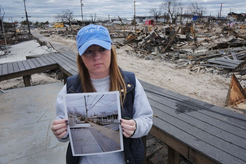 Meghan McGovern of the New York borough of Queens shows a photo of the scene behind her that she took Oct. 27, two days before superstorm Sandy arrived. A fire during the storm destroyed more than 100 homes in her neighborhood; hers survived. Residents of areas hit hard by Sandy would welcome the funds we now send abroad, a reader says.